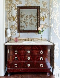 A vanity made from a Directoire commode furnishes the powder room of a Houston residence decorated by Elissa Cullman. The scenic Gracie wallpaper is hand-painted.