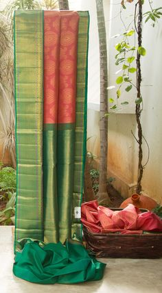 BRIGHT PINK KANCHIVARAM silk WITH zari floral MOTIFS ALL OVER THE BODY. THE solid zari BORDER AND PALLU IN Green AND GOLD COMPLETE THE PIECE