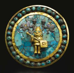 Moche Gold and Turquoise Inlay Ear Ornament ca. A.D. 200-500 -   the long cylindrical shaft surmounted by a gold frontal inlaid with a mosaic of turquoise, and decorated with an applied gold warrior composed of carefully fitted sheets, holding a club and shield, with turquoise eyes and earrings, and flanked above by two sodalite avian warriors also holding clubs. Diameter:  3 1/2  in (8.9 cm) Length: 3 3/4 in  (9.5 cm)
