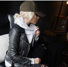 Olive hat, gray sweatshirt, leather jacket, black ripped jeans