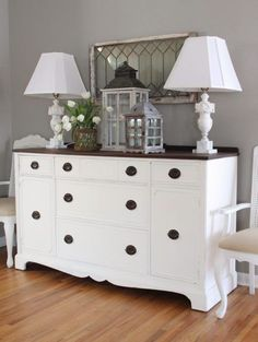Vintage dresser in the dining room in stark white and dark brown trim. This area looks pleasant with a beautiful array of rustic decor and fresh flowers.