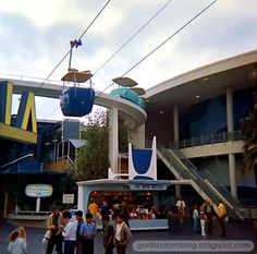 Perpetual Vintage Disneyland Motion: The New Tomorrowland's PeopleMover track crosses over the Skyway path above the Mod Hatter as the Carousel of Progress revolves beyond. The edge of the Autopia sign peeks in on the left.