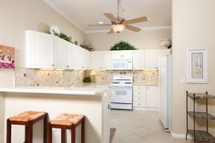 Light and bright eat-in kitchen with breakfast bar and tumbled marble backsplash.