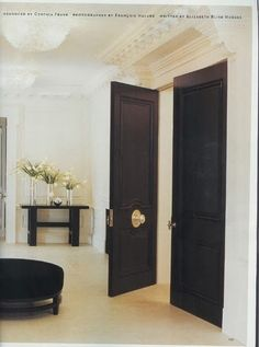 foyer with punch of black double doors and centered brass hardware.