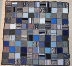 A warm wool blanket in boy colors of blues and grays. This blanket quilt was constructed of dozens of recycled wool sweaters. I blanket stitched the