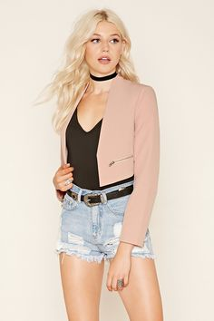 A woven blazer featuring padded shoulders, open front, long sleeves, mock zippers, and a cropped silhouette.