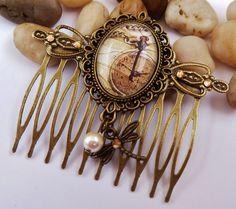 Dieser romantische Haarkamm besteht aus bronzefarbenem Metall und einer filigranen Fassung. Der handgearbeitete Glas-Cabochon zeigt ein wunderschön...