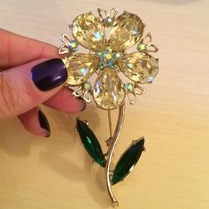 "Vintage Dodds Large Rhinestone Flower Pin This vintage Dodds pin features delicate yellow pear shaped rhinestone petals with a light blue aurora borealis center and accents, and deep emerald green leaves at the stem. Measures approximately 3 1/2"" long and the flower measures 1 1/2"" wide.  Back side reveals foil back and a secure clasp .In excellent vintage condition. Vintage Jewelry"