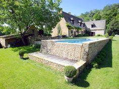 Le débordement par l'esprit piscine  9 x 3 m . Revêtement gris clair . Margelles en pierre naturelle de Vèze . Mur de débordement en lauze .
