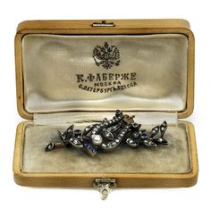 A gold, diamond, sapphire and pearl presentation brooch, Fabergé, Moscow, 1898-1908, formed as a laurel branch set with rose-cut diamonds and sapphire berries, applied with a lyre topped with gold Imperial crown, in a fitted box lined with cream velvet and silk and stamped with Fabergé logo, 56 standard, length: 4.5cm (1 3/4in).