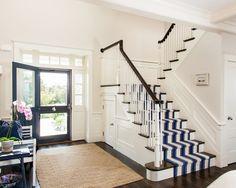 Entryway with navy door, white and navy striped stair runner, natural fiber rug, dark wood floors, white walls | Lewis & Weldon Custom Kitchens