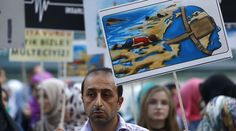 A man holds a poster with a drawing depicting drowned Syrian toddlers during a demonstration for refugee rights in Istanbul, Turkey, September 3, 2015. © Osman Orsal