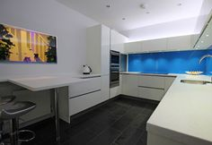 A handleless white gloss lacquer kitchen with corian worktop and full glass splashback behind the sink run and hob run. The blue splashback has been accentuated with lighting to reflect off its gloss surface, emphasising its bold colour and deep shine.