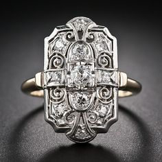 A sparkling Art Deco dinner ring ornately crafted in two-tone gold with lovely decorative, diamond-dotted, open scrollwork framing a central...