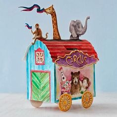 """The Sweet Paul Magazine website offers a free collection of circus papercraft. The templates in the collection are unique in that they are scans of hand-painted watercolors rather than the digitally produced images one usually sees. Included in the collection are the circus wagon pictured, as well as mini clown masks, playful monkey """"drink buddies"""", and Rosamunda, a dancing elephant automata"""