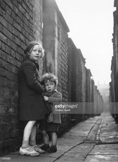 A little boy clutches his sister's coat in a narrow alleyway in the deprived Hulme area of Manchester. Original Publication: Picture Post - 6871 - Best And Worst Of Our Cities : Manchester - pub. 1954