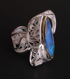 Russian Filigree Ring: 22k gold, sterling, fine silver, Koroit opal. Victoria Lansford, is a jeweler specializing in Russian Filigree. Detailed, swirly filigree work, and Lansford hand sculpts each section of her one-of-a-kind pieces.
