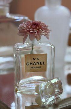 Bathroom styling - basket of cotton balls, hand cream, tissues, flowers in empty perfume bottles.