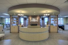PalmerCare Chiropractic, Sterling, VA - Close-up view of the reception desk, with signage, waterfalls, and backless shelving | Synergy D&C, Reston, VA