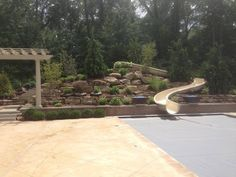 Hardscaping around this waterslide gives the pool an exotic feel! Great job by our friends at Beyond Landscaping!