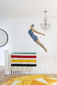 Toronto Textile designer Bev Hisey and Dan MacKenzie's Toronto home renovation. The landing at the top of the stairs — an original Jansen swimsuit swimmer signage from Vancouver, a family  chandelier, [Hudson Bay] blanket and gem carpet designed by Bev.