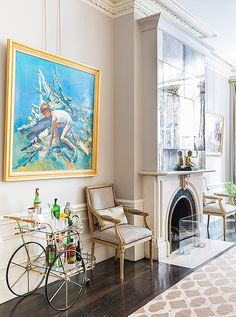 A vibrant blue painting makes even more of an impact when framed in gleaming gold (that matches the bar cart and Louis-style arm chairs below! Round Tufted Ottoman, Parisian Decor, Parisian Chic, Herringbone Wood Floor, Mirrored Side Tables, Vintage Bar Carts, Bar Cart Styling, Design Salon, Metal Tree Wall Art