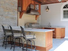 Family-Friendly Entertaining  Designer Laura A. Suglia-Isgro mixed a variety of long-lasting and natural materials to create this family-friendly outdoor kitchen. The wood-paneled roof keeps the cooking area shaded and prevents the space from being affected by the harsh weather conditions of the snowbelt region.
