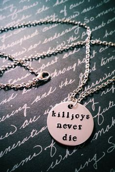 Hand stamped killjoys never die pendant necklace  Includes: 1 -- 1-inch brushed 14g aluminum circle pendant 1 -- 18-inch silver tone chain  *Charms may be added to this necklace upon selection  Please specify in comments IF: - You would like a 20 or 22-inch chain, if not the standard 18-inch chain will be sent.  Please read prior to purchase:  This piece is entirely hand crafted. I stamp each letter, one at a time, with extreme care. Please keep in mind that with hand stamping, the letters…