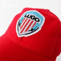 La gorra básica roja es una prenda ideal para los seguidores del CD Lugo.Es 100% algodón con tacto de terciopelo, orificios metálicos, sin costuras, visera pre-curvada con cierre metálico ajustable.    Es roja toda ella y con el reborde de la visera pre-curvada en blanco. En la parte frontal lleva un parche bordado con el escudo del Club Deportivo Lugo.