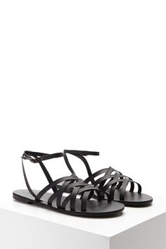 A pair of sandals featuring a strappy faux leather design, a buckle ankle strap, and a slight heel.