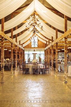 Love the setup of this rustic barn with the draping and twinkle lights--perfect for this Bluemont Vineyard wedding reception! | Photograph by Hay Alexandra Photography