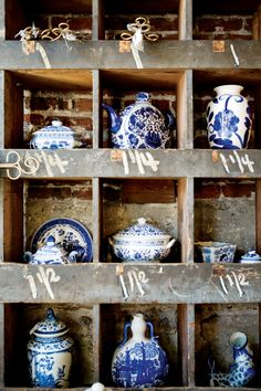 delicate blue + white porcelain contrasts beautifully with rough wooden shelves against and exposed brick wall