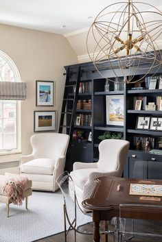 Beautiful group office space with built in bookcases and white armchairs | Duet Design Group