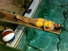 1950s: Woman wearing yellow swimsuit relaxing at the poolside
