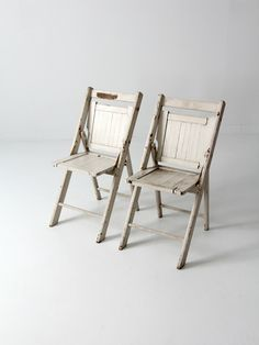 A pair of hard wood folding chairs with slat backs and seats circa 1950. Aged, white paint colors the chairs. A great pair of chairs! - set of 2 chairs - hard wood folding chairs with slat backs and s