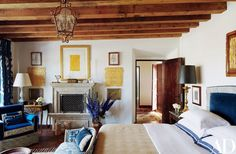 A watercolor by Fisher is mounted over the master bedroom's mantel, which is flanked by, from top, a pair of the designer's pencil drawings of seashells, two of his gilded tapestries, and a set of antique embroidery panels | archdigest.com