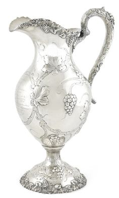 "An American sterling silver presentation wine ewer retailed by Rodgers & Krull, Louisville, KY, circa 1908 Of typical form with overall vintage decoration, vine entwined branch handle and domed foot, with inscription to front, ""Presented to / Wm. C. Johnson / by the National Association of / Life Underwriters...Louisville, Ky / Oct. 1909"", weight approximately 38 oz troy. height 15 1/2in (39cm); length 9 1/2in (24cm)"