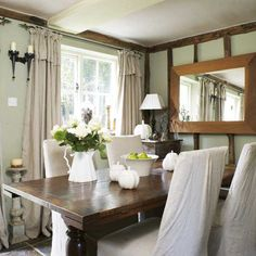english cottage dining room- I like the contrast with the dark table and white slip-covered dining chairs.