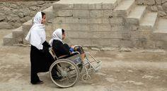Una niña de la escuela Sitara, en Kabul, empuja la silla de ruedas de su compaña, amputada de las dos piernas por la explosión de una mina. La Convención sobre los Derechos de las Personas con Discapacidades fue adoptada el 13 de diciembre de 2006. Foto: ONU/Hassan Zakizada.