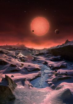 This artist's impression shows an imagined view from the surface one of the three planets orbiting an ultracool dwarf star just 40 light-years from Earth that were discovered using the TRAPPIST telescope at ESO's La Silla Observatory. These worlds have sizes and temperatures similar to those of Venus and Earth and are the best targets found so far for the search for life outside the Solar System. They are the first planets ever discovered around such a tiny and dim star. In this view one of…