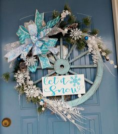 Wagon wheels used as home or barn wreaths are very popular. This light blue wagon wheel helps to capture a cold winter country feeling. The sign is blue with white glitter surrounding the Let It Snow lettering and pretty snowflake. This beautiful wreath is covered with wintery