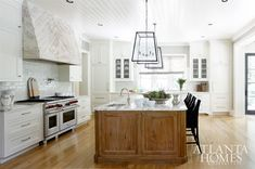 Light and open | oak island, white-washed kitchen,antique finish range hood, beautiful hardwood floor, clean design, structure, simple and chic lighting.