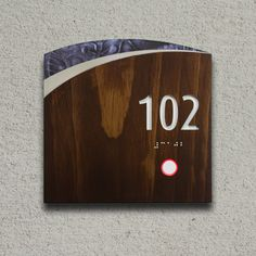 Custom hotel room number sign with solid wood shell with printed acrylic accents, relief-cut nbumbers, braille, doorbell and LED indicators for do-not-disturb and housekeeping.