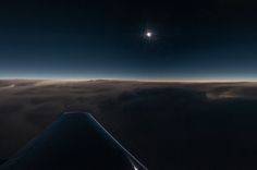 The wing of our Dassault Falcon 900B jet is visible in this wide angle photo taken during the instant of maximum eclipse where we had the diamond-ring effect. The moon's shadow appears across the clouds in a long, thin elliptical shape.