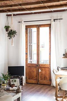 Apartamento rehabilitado en Barcelona con estilo rústico, aprovechando los materiales originales.