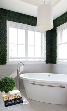 Amazing master bathroom features upper walls clad in faux boxwoods and lower walls clad in gray tiles lined with a corner tub placed under windows. Bathtub Decor, Bathroom Spa, Master Bathroom, Bathroom Ideas, Eclectic Bathroom, Bathroom Styling, Home Decor Shops, Diy Home Decor, Corner Tub
