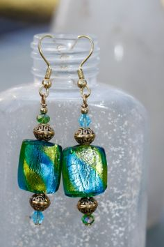 Blue and green foil inside clear glass. Gold filled spacers, Chinese and Swarovski crystals.  Gold plated head pin and ear wire. 2 3/8 inches from top of ear wire to bottom of earring. Please remember the glass beads are hand made and will vary in size! Comes wrapped in tissue paper in a gift bag...