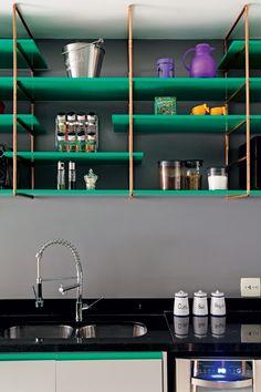 Laqueadas de verde, as superfícies de MDF têm estruturas de tubos de cobre – material com que o proprietário trabalha. A cor se repete em detalhes do gabinete da pia (Foto: Edu Castello/Editora Globo)