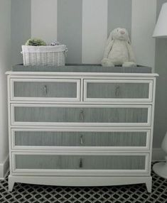 This is a gray-striped vignette created by stylish young New York designer, Sara Gilbane. I feel the simplicity of this changing-table chest moves the Gustavian gray furniture concept forward, modernizing  and punching it up with the gray and white tent-stripe wall. The texture is great and the tassel-drop handles so chic.