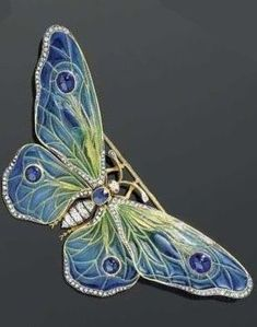 AN ART NOUVEAU ENAMEL, DIAMOND, SAPPHIRE AND RUBY BROOCH, ca. 1890. Designed as a butterfly, the wings mounted en tremblant, the body set with one oval sapphire and old-mine-cut diamonds. The wings decorated with plique-à-jour enamel in blue-green tones, and set with four sapphire cabochons. The wing borders partially set with rose-cut diamonds. Probably of French.